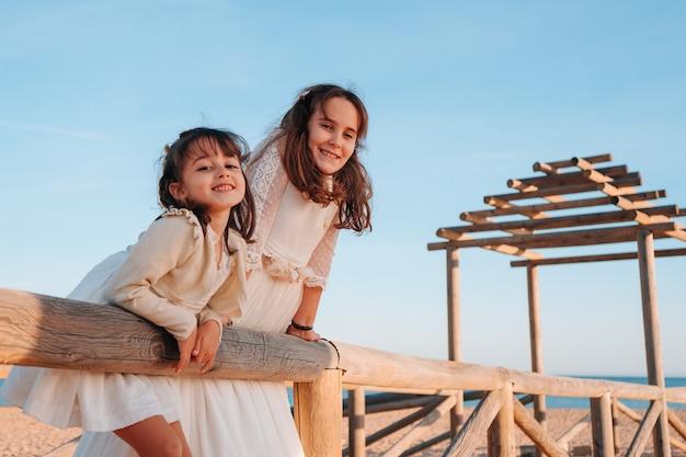 Feliz hermanas caucásicas apoyado en un poste de madera en la playa