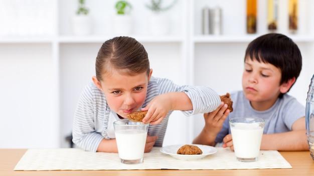 Feliz hermano y hermana comiendo galletas y bebiendo leche