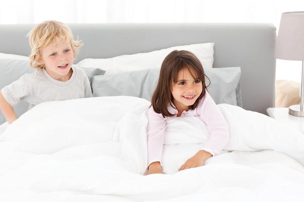 Feliz hermano y hermana jugando en el dormitorio de sus padres