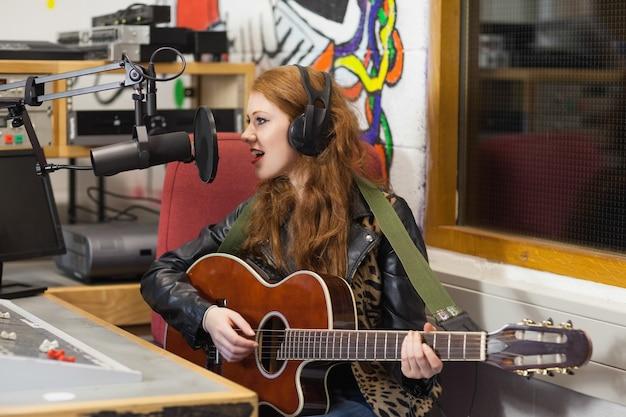 Feliz hermosa cantante grabando y tocando la guitarra