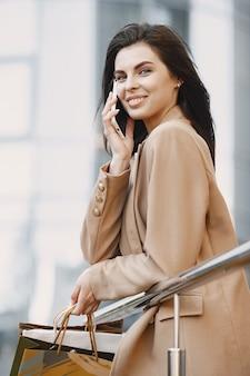 Feliz hermosa joven con bolsas de la compra, hablando por un teléfono móvil de un centro comercial