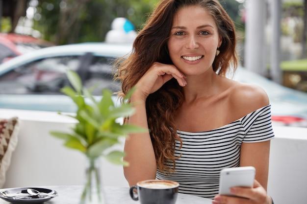 Feliz hermosa joven con encantadora sonrisa cálida, instala una nueva aplicación en un teléfono inteligente moderno