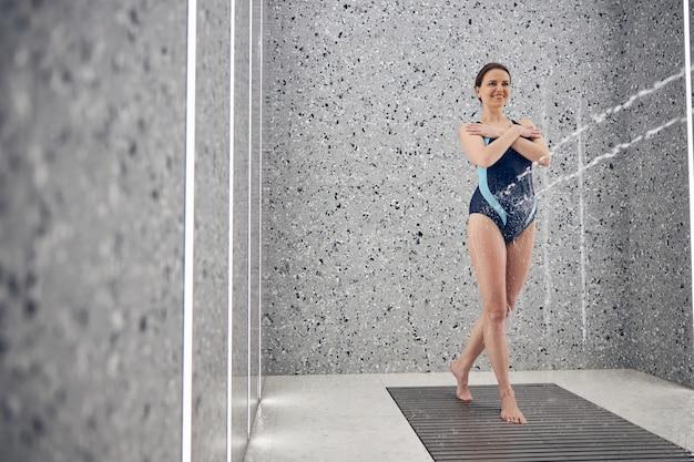 Feliz hermosa joven esbelta de pie con los brazos cruzados durante un masaje con agua a alta presión