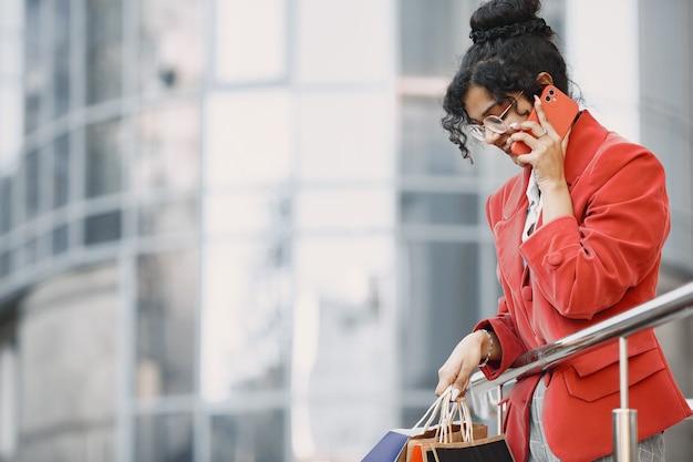 Feliz hermosa joven con gafas, con bolsas de la compra, hablando por un teléfono móvil de un centro comercial