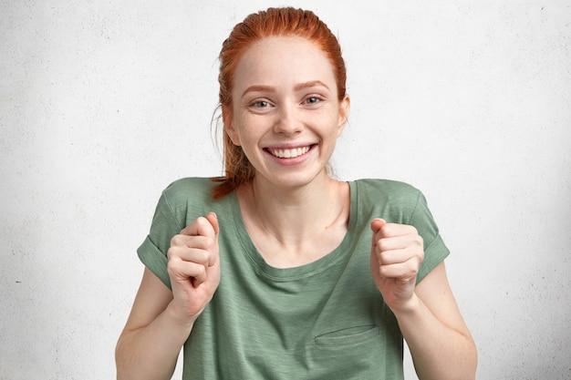Feliz hermosa joven pelirroja llena de alegría celebra el concurso ganador, vestida con una camiseta informal, tiene una amplia sonrisa, aislada sobre hormigón blanco