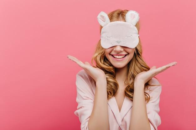 Feliz hermosa joven posando en eyemask. chica europea alegre en pijama de pie en la pared rosa en antifaz para dormir en la mañana.