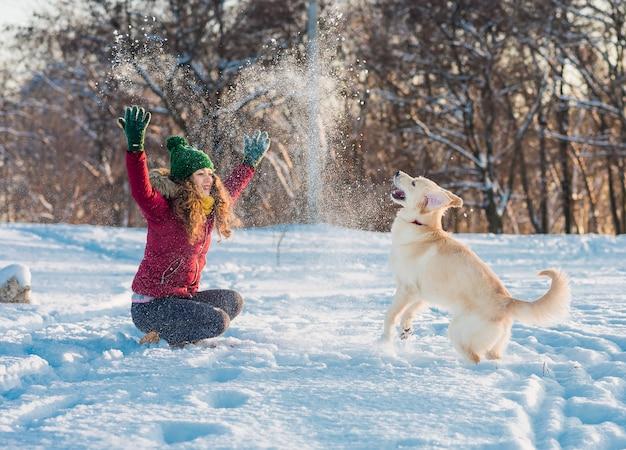 Feliz hermosa joven soplando copos de nieve de sus manos a su perro golden retriever en un día de invierno