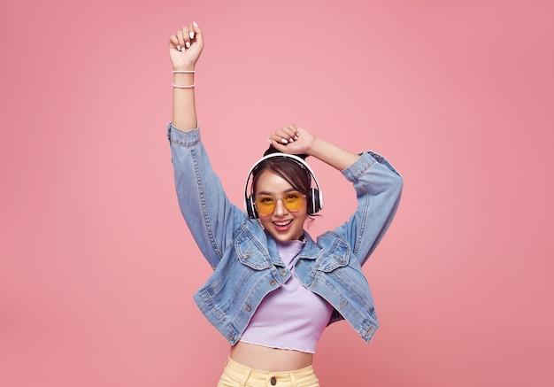 Feliz hermosa mujer adolescente asiática en gafas amarillas escuchando música en auriculares y baile en la pared rosa.