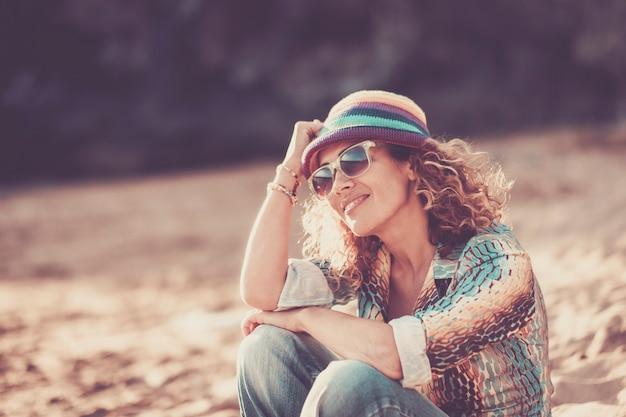 Feliz hermosa mujer alegre sentada en la playa y disfrutando del horario de verano