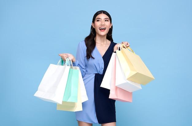 Feliz hermosa mujer asiática adicta a las compras con vestido azul y sosteniendo bolsas de compras aisladas en la pared azul.
