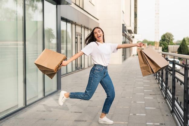 Feliz hermosa mujer con bolsas de colores en la mano saltando alegremente en el aire.
