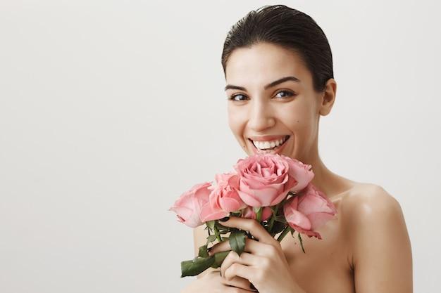 Feliz hermosa mujer desnuda, riendo mientras recibe ramo de rosas