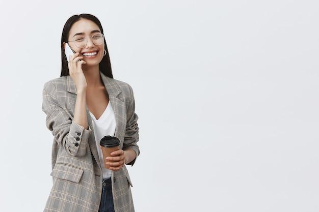 Feliz hermosa mujer elegante con gafas y chaqueta, sosteniendo una taza de café y un teléfono inteligente, teniendo una conversación divertida, disfrutando de un gran día