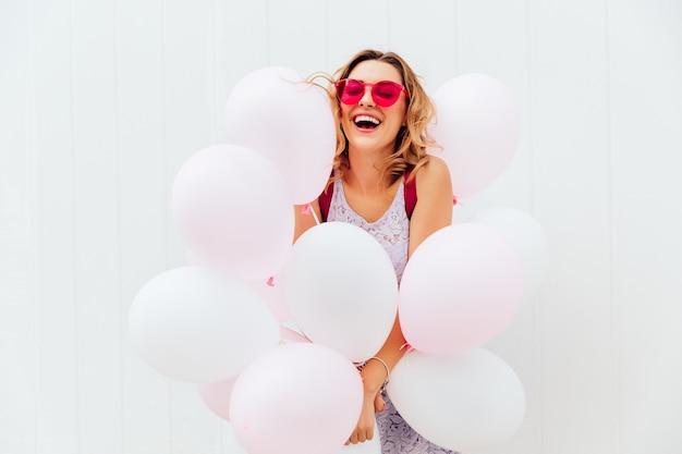 Feliz hermosa mujer joven en gafas de sol de color rosa tiene globos blancos, sonriendo alegremente