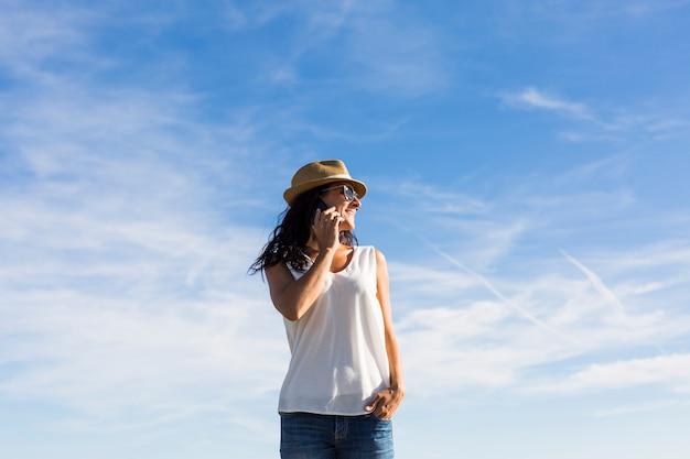 Feliz hermosa mujer joven hablando por su teléfono móvil al atardecer. fondo de cielo azul al aire libre. estilo de vida