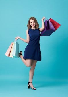 Feliz hermosa mujer joven en vestido azul y bolso de compras de mano