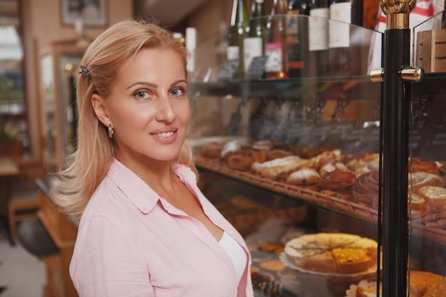 Feliz hermosa mujer madura sonriendo a la cámara mientras compra en la panadería