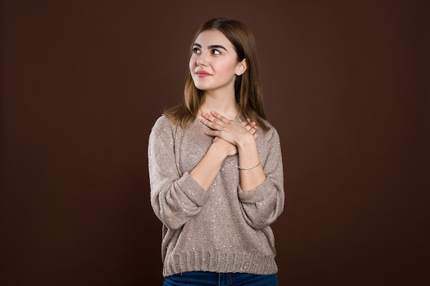 Feliz hermosa mujer mira a un lado, viste un suéter cálido, sueña con una cita con un chico guapo