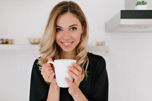 Feliz hermosa mujer rubia caucásica en ropa de dormir bebe café en la cocina y sonríe a la cámara en casa se despierta por la mañana en un día soleado.