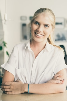 Feliz hermosa mujer rubia vestida con camisa blanca, de pie en el espacio de trabajo conjunto, apoyado en el escritorio