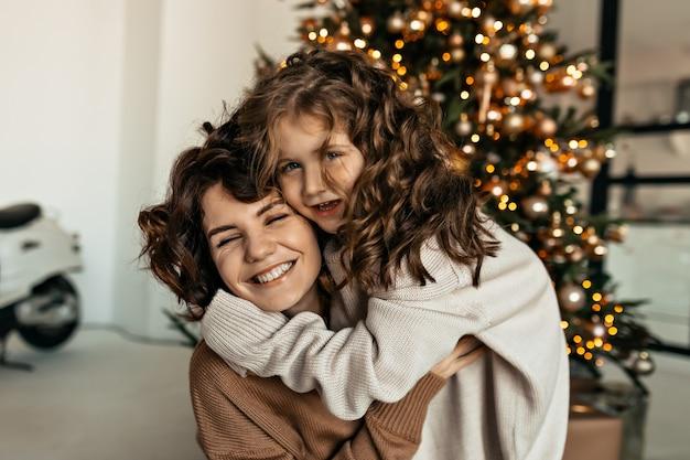 Feliz hermosa mujer con su pequeña hija linda con el pelo ondulado abrazándose y divirtiéndose delante del árbol de navidad