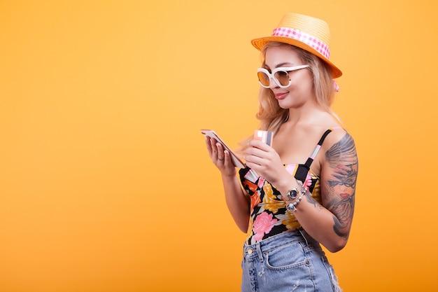 Feliz hermosa mujer tiene teléfono inteligente y tarjeta de crédito, en estudio sobre fondo amarillo