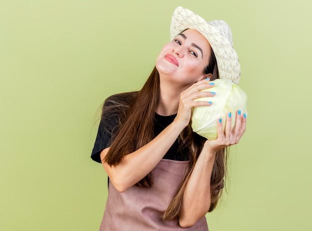 Feliz hermosa niña jardinero en uniforme con sombrero de jardinería sosteniendo repollo alrededor de la cara aislado sobre fondo verde oliva