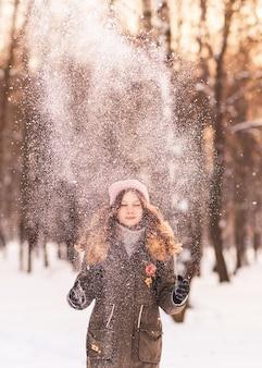 Feliz hermosa niña juega con nieve en el parque en un día soleado