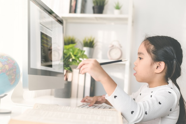 Feliz hermosa niña pequeña estudiante usando una computadora para estudiar a través de e-learning en línea