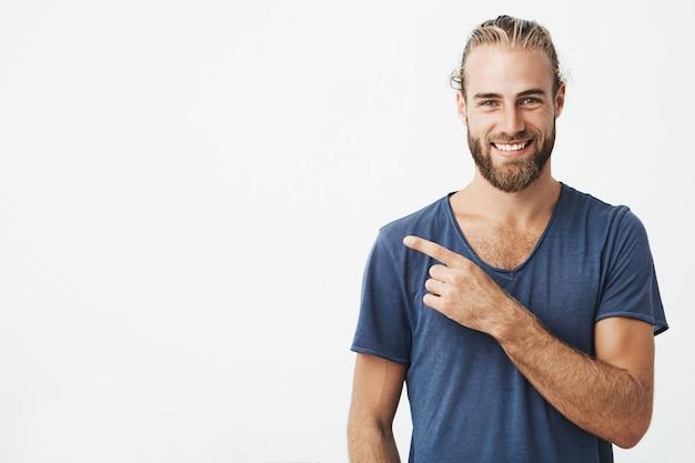 Feliz hermoso chico barbudo con peinado guapo, sonriendo y señalando copyspace