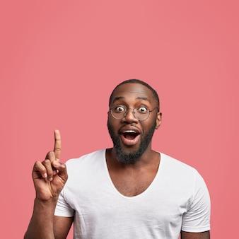 Feliz hombre adulto afroamericano positivo tiene piel oscura y barba espesa