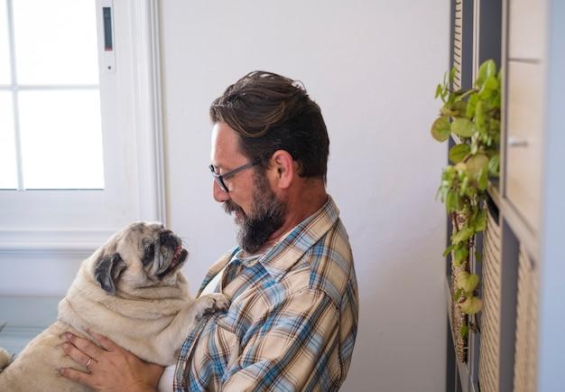 Feliz hombre adulto hipster abrazar y jugar con su viejo mejor amigo perro pug en casa