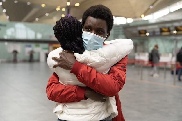Feliz hombre africano en máscara abrazo a mujer que llega de viaje en el aeropuerto