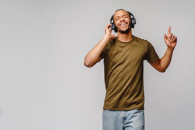 Feliz hombre africano sonriendo escuchando música en auriculares sobre pared gris