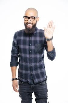 Feliz hombre afroamericano agitando la mano aislado en una pared blanca