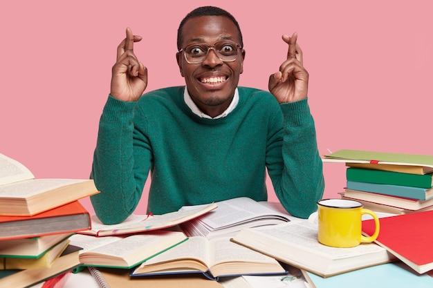 Feliz hombre afroamericano con amplia sonrisa, dientes blancos mantiene los dedos cruzados, cree en la buena suerte, lee literatura, bebe té caliente de una taza amarilla