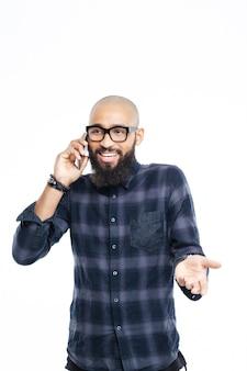 Feliz hombre afroamericano hablando por teléfono aislado en una pared blanca