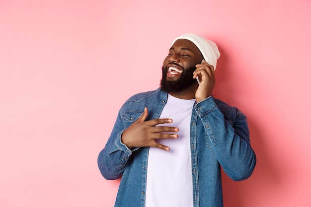 Feliz hombre afroamericano hablando por teléfono móvil, riendo y sonriendo, de pie en gorro y camisa de mezclilla sobre fondo rosa
