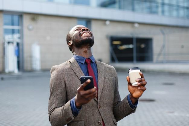 Feliz hombre afroamericano parece suerte leyendo algo en su teléfono inteligente