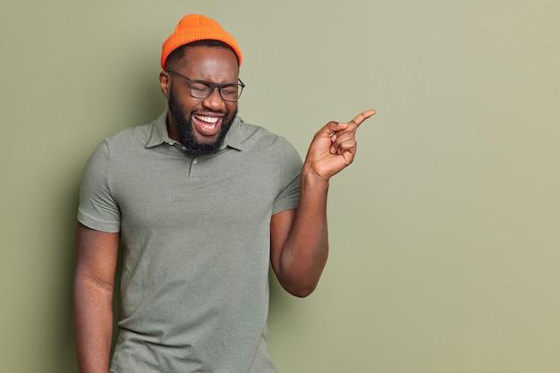 Feliz hombre afroamericano se ríe alegremente apunta lejos muestra algo fresco y divertido viste sombrero y camiseta casual gafas transparentes posa en el estudio demuestra espacio de copia