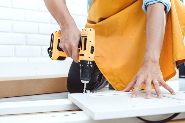 Feliz hombre asiático mejoras para el hogar montaje de muebles lee instrucciones y aprieta el tornillo con un taladro.