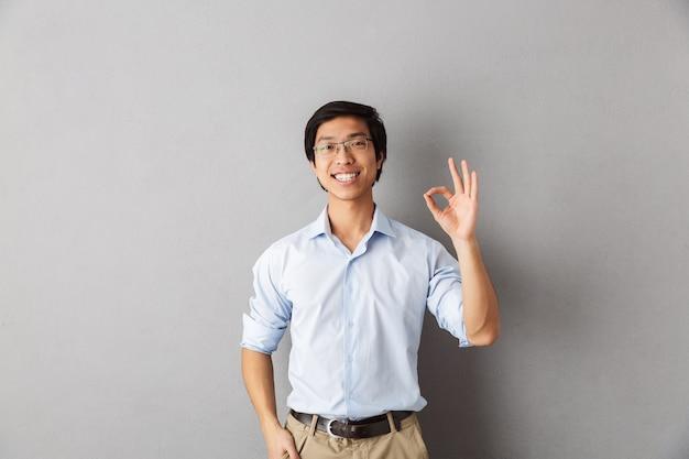 Feliz hombre asiático de pie aislado, mostrando ok