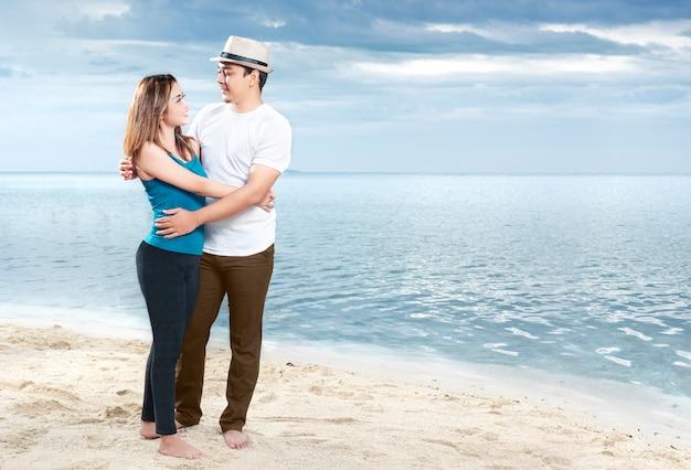 Feliz hombre asiático con sombrero abrazando a su novia en la playa