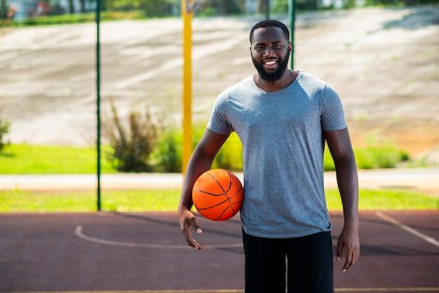 Feliz hombre barbudo en cancha de baloncesto