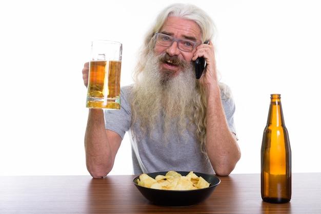 Feliz hombre barbudo senior sonriendo y hablando por móvil