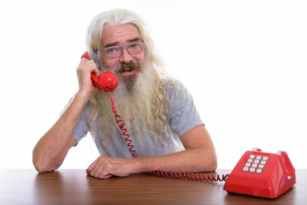 Feliz hombre barbudo senior sonriendo mientras habla por teléfono