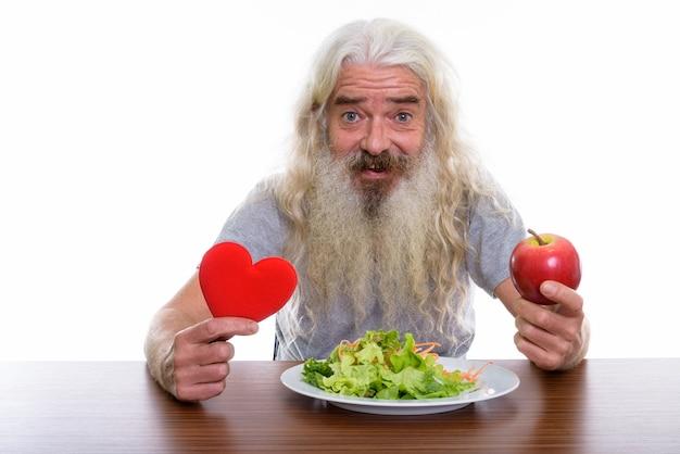 Feliz hombre barbudo senior sonriendo mientras sostiene el corazón rojo