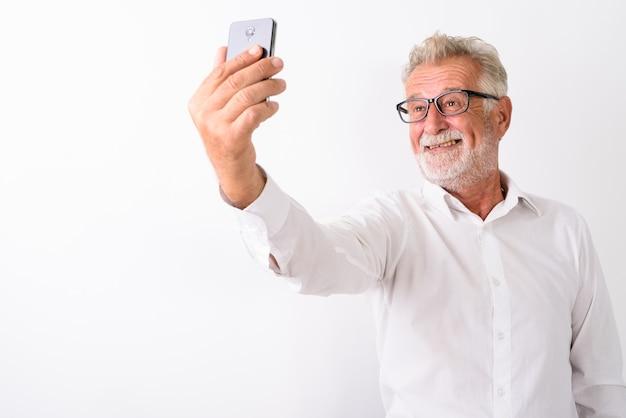 Feliz hombre barbudo senior sonriendo mientras toma una foto selfie con teléfono móvil mientras usa anteojos en blanco