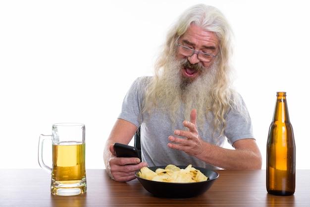 Feliz hombre barbudo senior sonriendo mientras usa el móvil