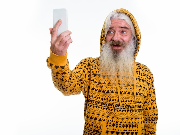 Feliz hombre barbudo senior sonriendo mientras usa sudadera con capucha
